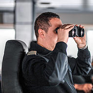 Captain with a pair of binoculars on the bridge.